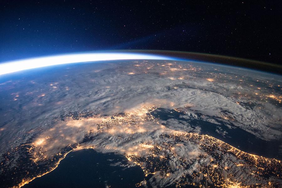 Городские огни, облака, свечение атмосферы и и солнечного света, увиденные с орбиты Земли над Южной Европой.