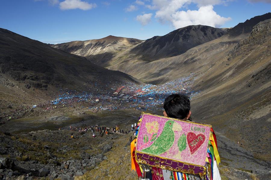 """Мальчик спускается с горы, глядя на десятки тысяч паломников, которые собрались чтобы отпраздновать трехдневный фестиваль """"снежной звезды"""" в Перу, 24 мая 2016."""