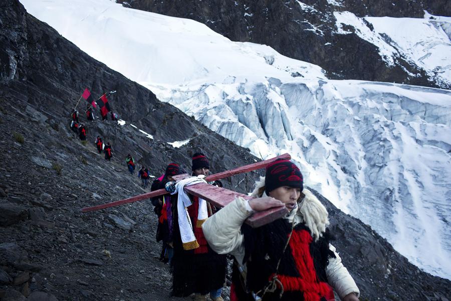 Мужчины спускаются к леднику неся крест, в последний день фестиваля, 24 мая 2016 года.
