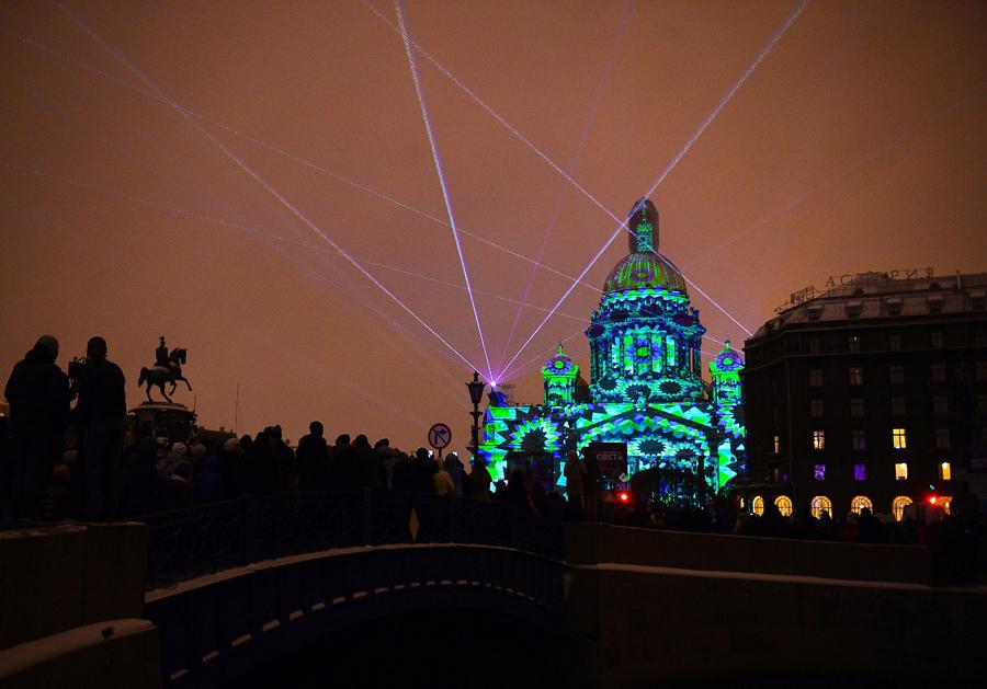 Люди наблюдают за световым шоу проецируемого на знаменитый Исаакиевский собор во время Фестиваля огней в Санкт - Петербурге, 4 ноября 2016 года.