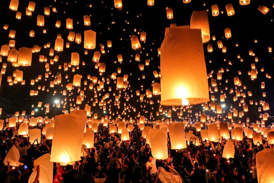 Люди запускают летающие фонарики во время фестиваля Йи Пенг в северной столице Чиангмае, Таиланд, 14 ноября 2016 года.