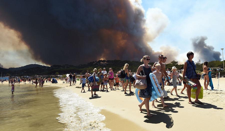 Люди покидают пляж со своими вещами, после возгорания леса в Борм-ле-Мимоза, на юго - востоке Франции, 26 июля, 2017.