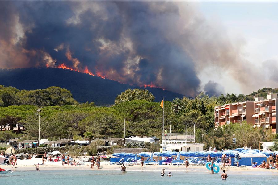 Пламя и дым заполнили небо над холмом, тем временем туристы плавают на пляже в Борм-ле-Мимоза, Франция, 26 июля, 2017.
