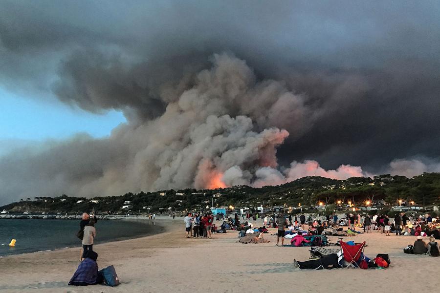 Эвакуированные люди стоят на пляже и смотрят на пожар, горящий лес в Борм-ле-Мимоза, на юге Франции, 26 июля 2017.