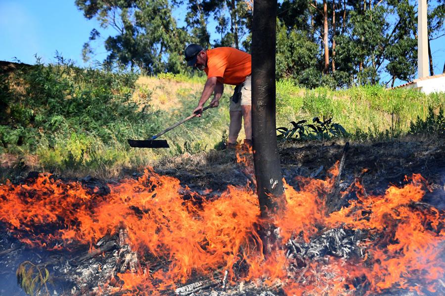 Мужчина пытается потушить огонь.