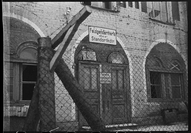 Огороженное проволокой здание немецкой комендатуры на Красной улице в Гатчине. Ленинградский фронт, 1943 год: