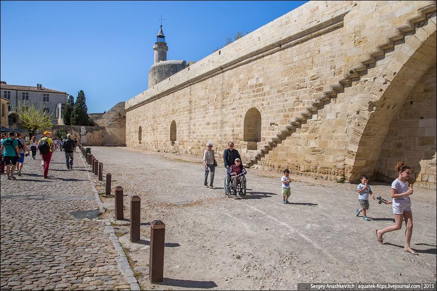 Людовик IX заложил первую сторожевую башню с маяком (Tour de Constance), а его потомки уже позже построили четырехугольную крепостную стену со сторожевым проходом сверху, с 20 зубчатыми башнями и 10 воротами.