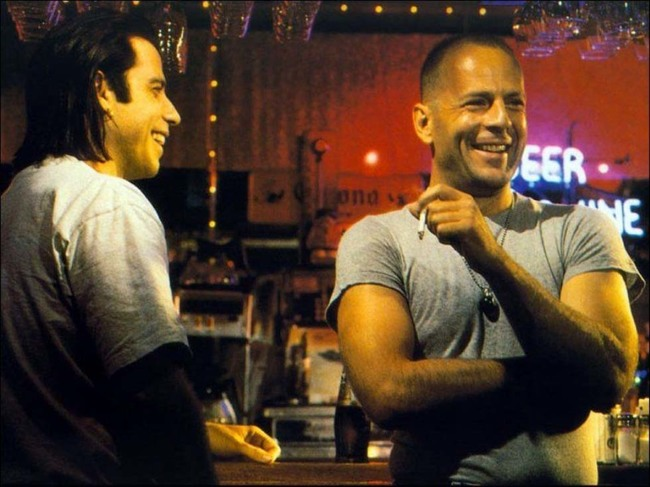 Джон Траволта и Брюс Уиллис смеются о чем-то между сценами.
