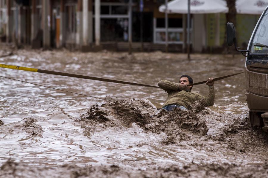 Человек цепляется за веревку, чтобы пересечь затопленную улицу вышедшую из берегов реку Копьяпо,  после обильных осадков, которые затронули некоторые районы города в Копьяпо, Чили.