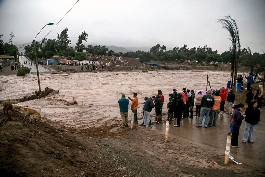 Люди наблюдают за разлитой рекой Копьяпо из-за обильных осадков в городе Копьяпо, Чили
