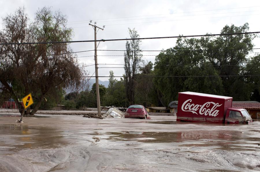 Автомобили и грузовик  наполовину погруженные в грязь в Копьяпо, Чили.