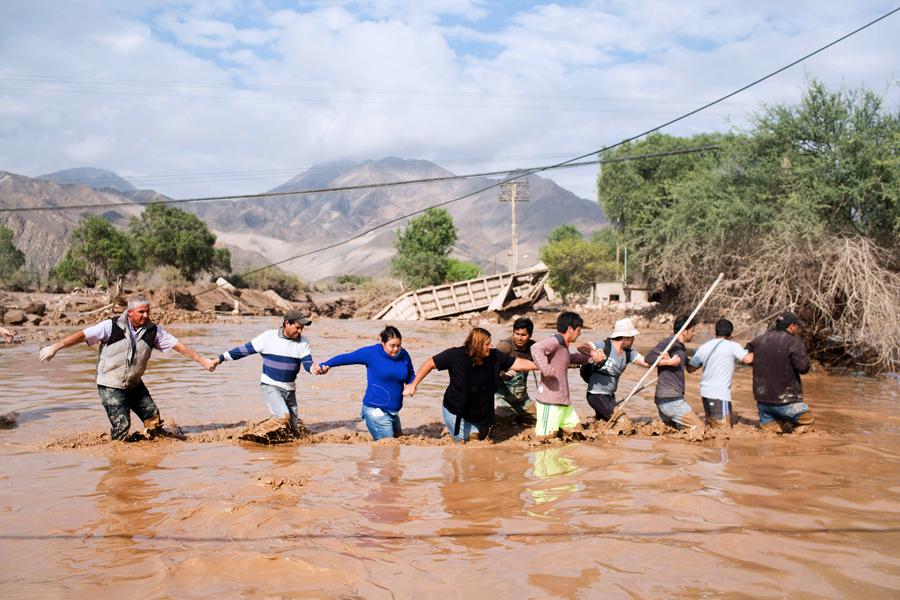 Местные жители переходят дорогу затопленную проливными дождями недалеко от города Копьяпо, Чили.