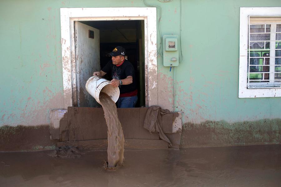 Мужчина опустошает свой дом затоплен проливными дождями в Копьяпо, Чили.