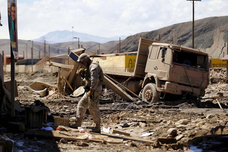 Солдат патрулирует местность, затопленную водой, в Диего де Альмагро.