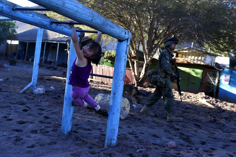 Девочка играет на территории детской площадки, покрытой засохшей грязью в городе Сан-Антонио ( San Antonio), Чили.