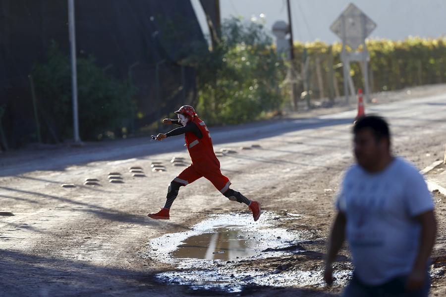 Доброволец, одетый, как клоун прыгает через лужу на одной из улиц города Сан-Антонио, 7 апреля 2015г. Волонтер был одет, чтобы выступить на шоу для детей в пострадавших от наводнения.