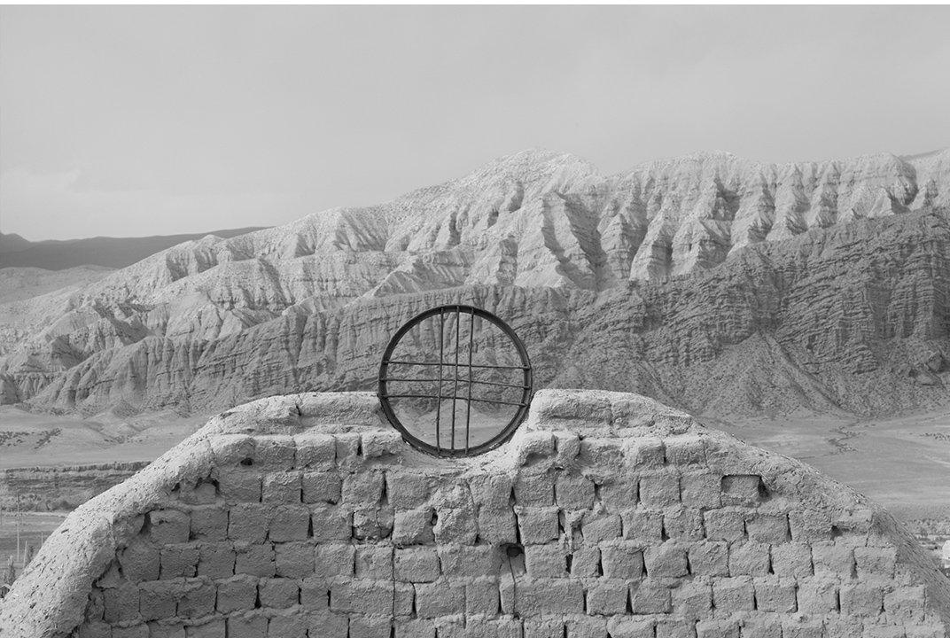 Киргизское погребальное сооружение имитирует округлость горы позади него.