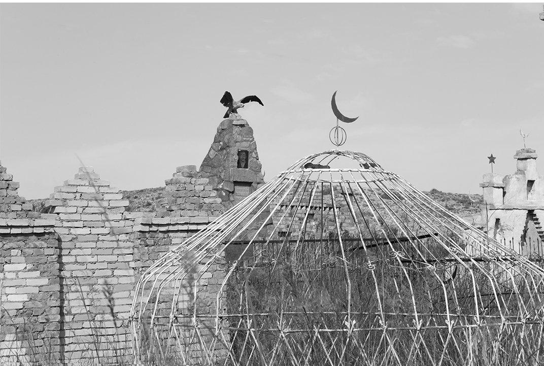 Юрта, переносная круглая хижина, была частью центрально-азиатской кочевой культуры на протяжении веков. В советские времена металл был в изобилии и по дешёвке, поэтому металлические юрты встречались намного чаще кладбищах. Исламский полумесяц на вершине этой юрты, и орел расправляющий крылья.