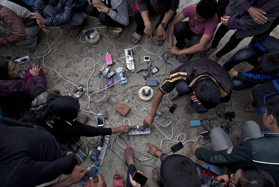 Непальские люди заряжают свои сотовые телефоны на открытой местности в Катманду.