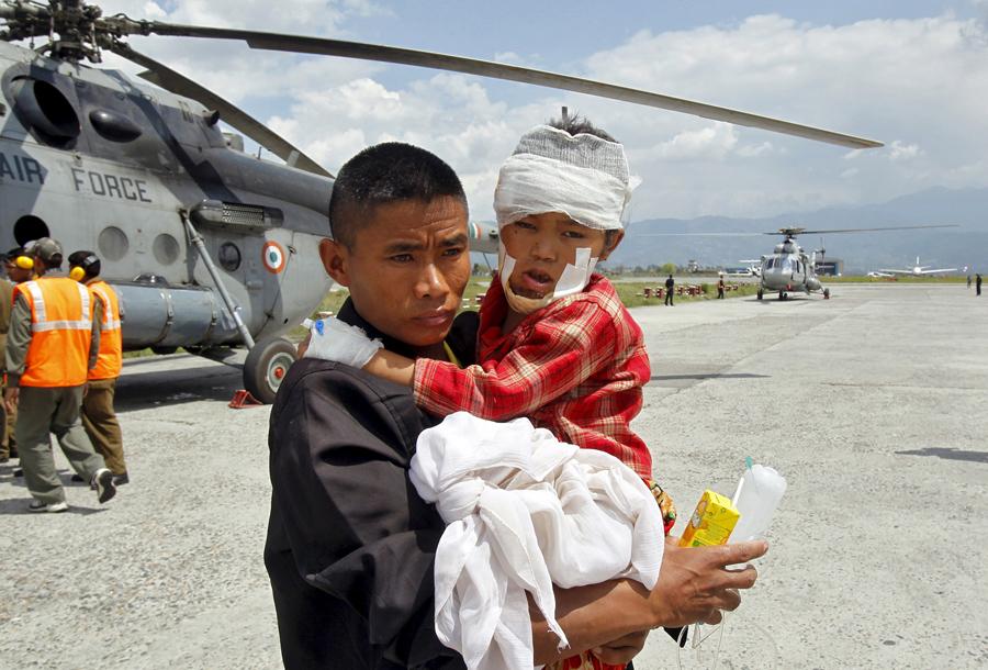 Мужчина несёт раненого ребенка.
