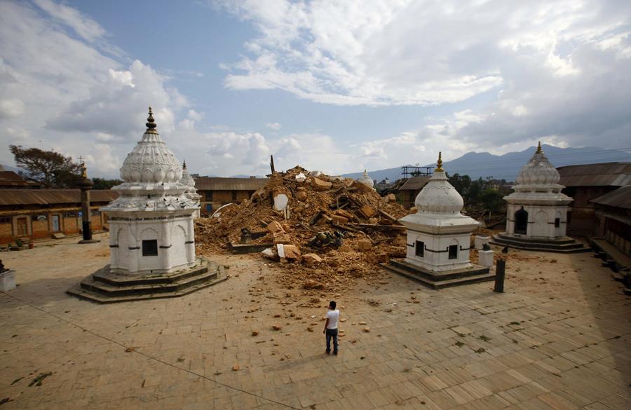 Местные жители смотрят на обломки древнего храма, после того, как он получил повреждение в землетрясении.