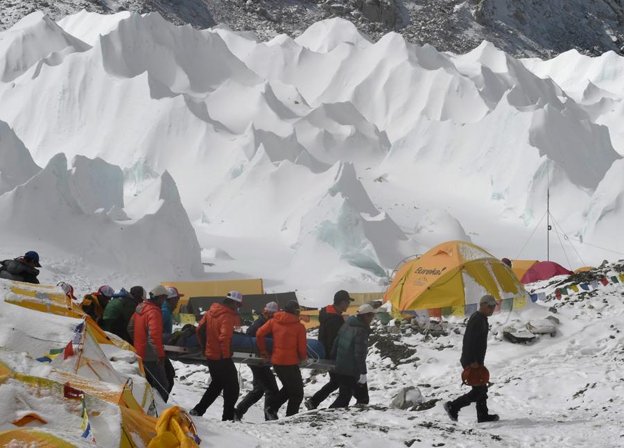 Спасательная команда несет раненого человека в сторону спасательного вертолета в лагерь у Эвереста. 26 апреля 2015 года, после схода лавины, вызванное землетрясением, всё покинули лагерь.