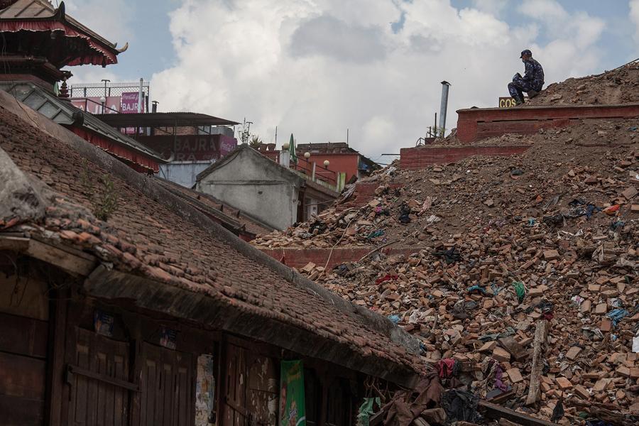 Спасатель сидит на обломках обрушившегося храма на площади Дурбар.