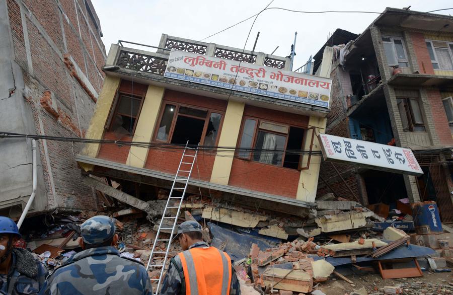 Непальские спасатели наблюдают за поврежденным зданием после землетрясения в Катманду.