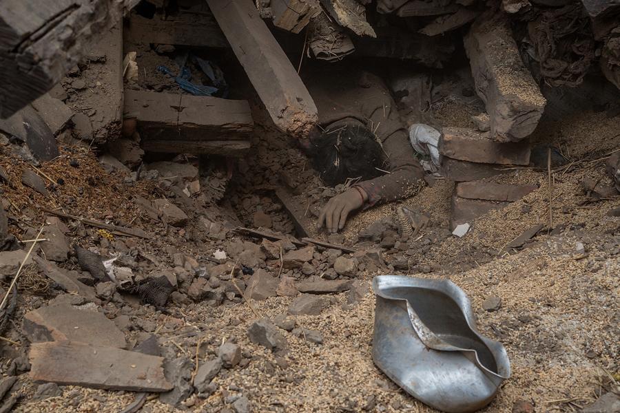 Тело жертвы землетрясения в Непале, лежит под обломками одного из разрушенных зданий г. Бхактапур.