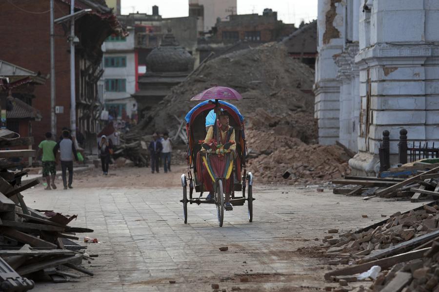 Мужчина крутит педали, проезжая мимо поврежденных зданий на площади Дурбар в Катманду.
