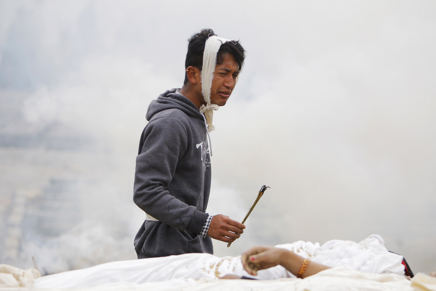 Мужчина выполняет ритуал во время кремации его матери, которая умерла в ходе землетрясения в Бхактапур, рядом с Катманду.