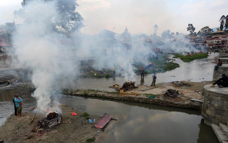 Люди сжигают тела жертв землетрясения, на массовой кремации в Пашупатинатх в Катманду.