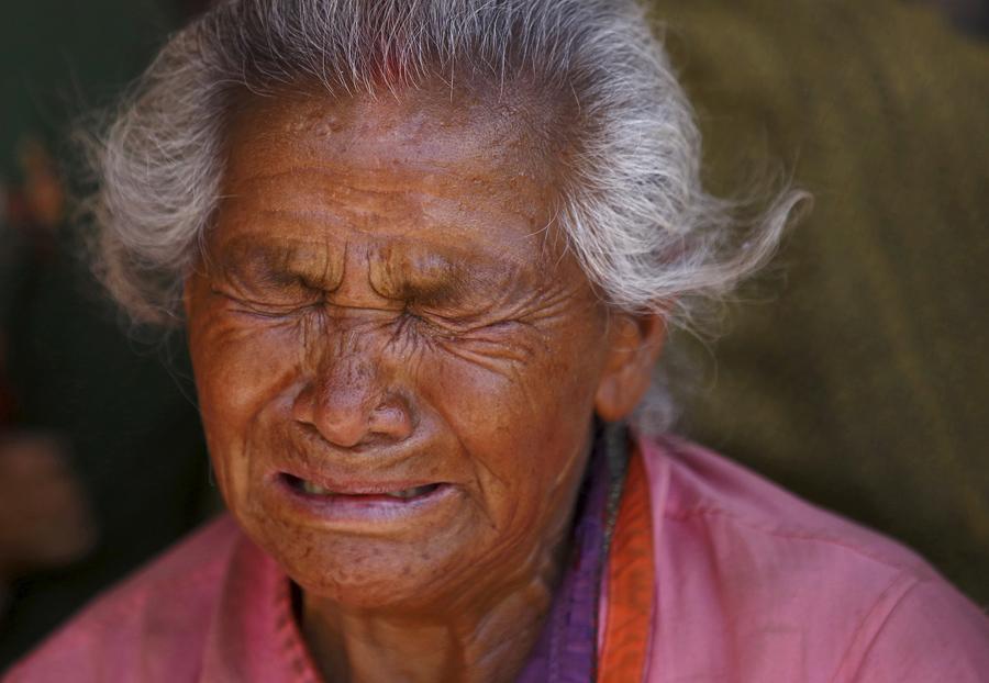 Женщина оплакивает свою внучку, которая умерла при землетрясении.