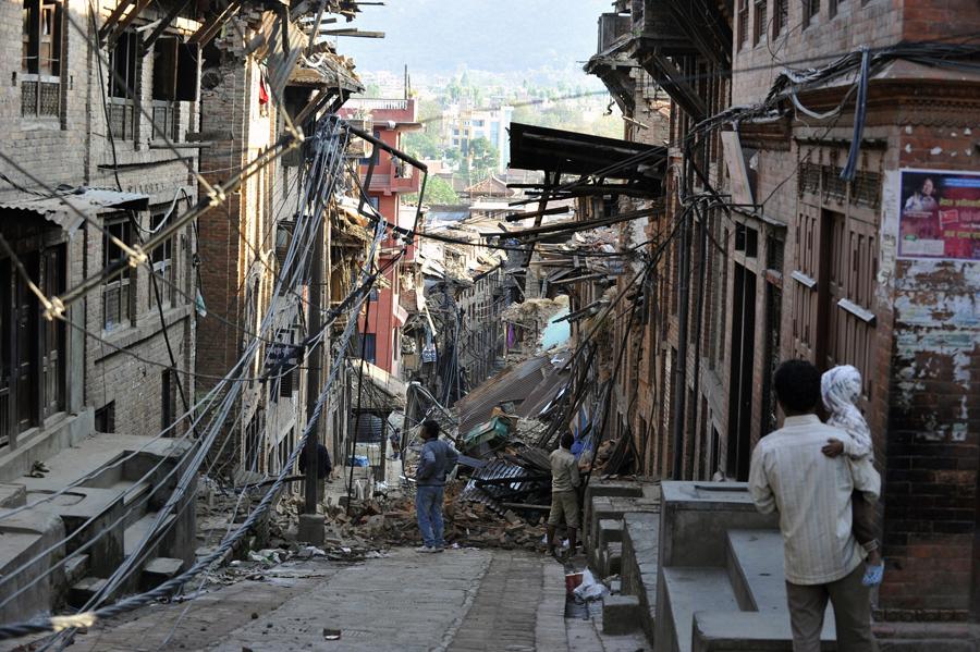Жители смотрят на разрушенные дома в Бхактапуре, на окраине Катманду.