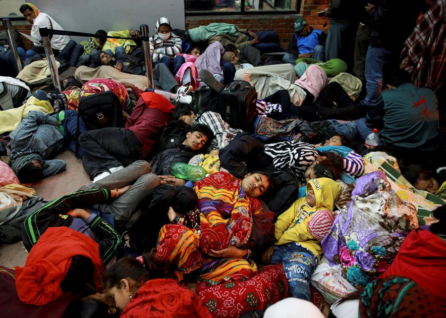 Люди спят у терминала ожидая вылета, в аэропорту в Катманду.