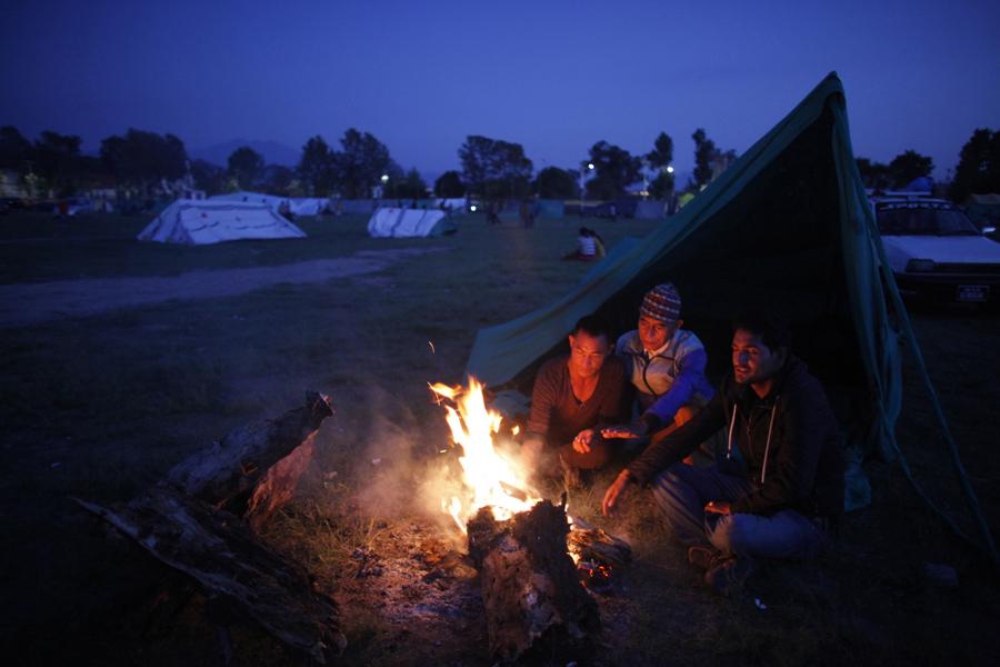 Местные жители греются у костра и остаются на открытом пространстве опасаясь новых толчков в Катманду, Непал. 2015 год.