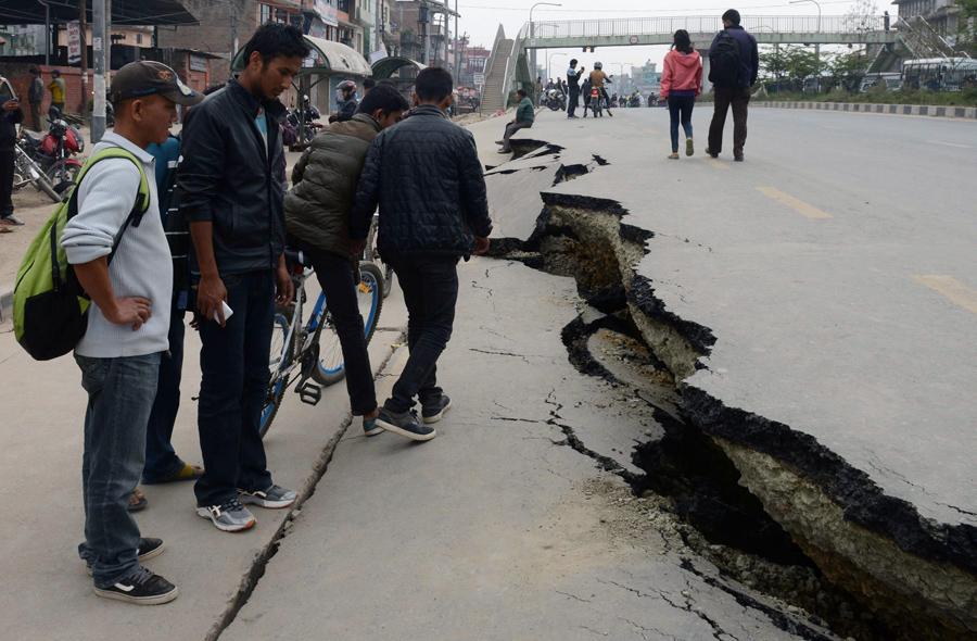 Непальские жители проходят мимо поврежденного дорожного полотна после землетрясения в Катманду.