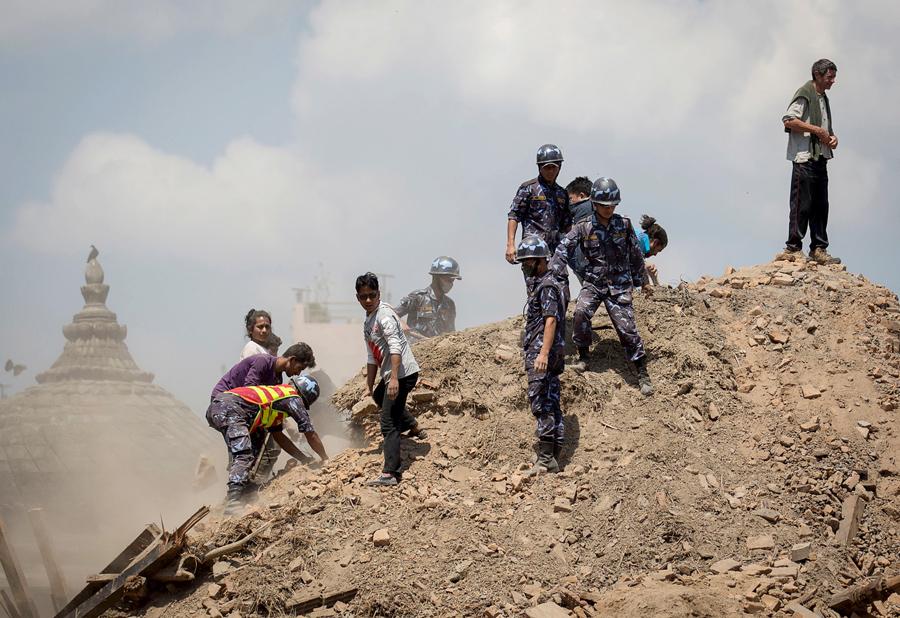 Непальская полиция и добровольцы расчищают развалины, в поисках выживших у разрушенного храма в Катманду.