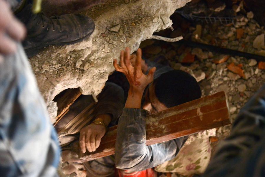 Спасатели помогают мужчине который попал в ловушку после землетрясения.