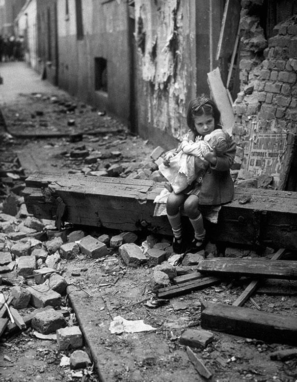 Маленькая девочка с плюшевым зайцем, сидит на развалинах своего разбомбленного дома, Лондон, 1940 г.