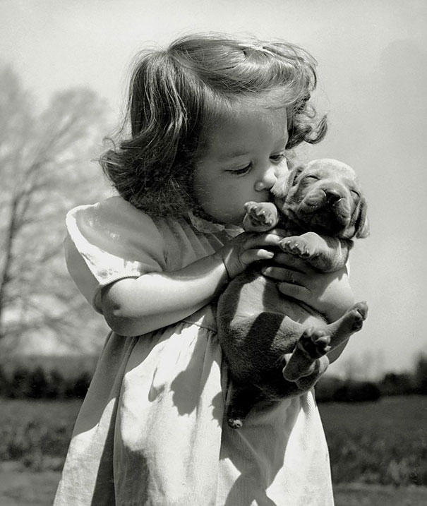 Девочка целует щенка.