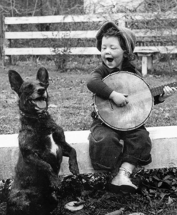 Девочка играет, собака подпевает.