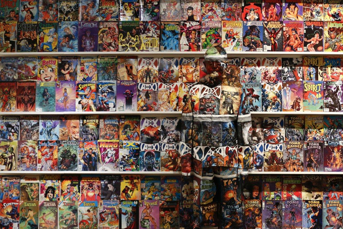 """Если вы посмотрите с близкого расстояния, вы увидите Лю Болина (Liu Bolin), китайского художника, известного как """"человек-невидимка"""" который слился со стендом комиксов."""