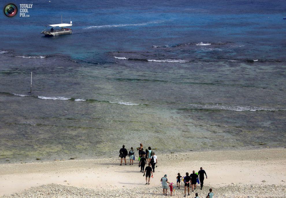 """Туристы готовят лодки, чтобы плавать в районе под названием """"коралловые сады""""."""
