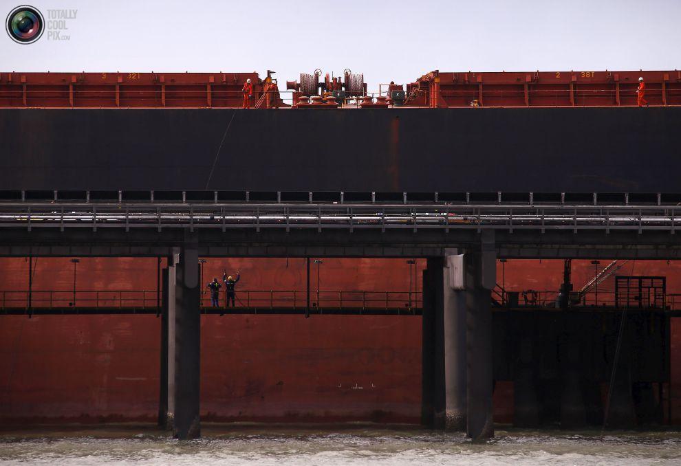Рабочие в порту грузят судно с углем на РГ Танна угольного терминала расположенном в городе Гладстон в штате Квинсленд, Австралия.