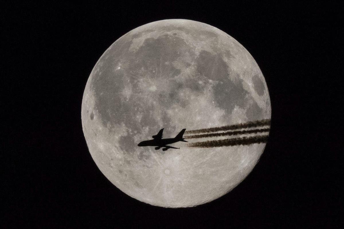 Самолет на фоне полной луны. (Фото: ZSOLT CZEGLEDI)