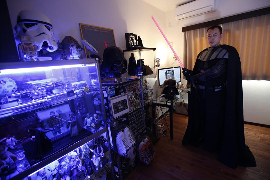 Мужчина по прозвищу Ikemasa, 37 лет, не захотел называть своё настоящее имя позирует для фото в одежде Дарта Вейдера рядом со своей коллекцией в Токио, Япония, 4 декабря, 2015.