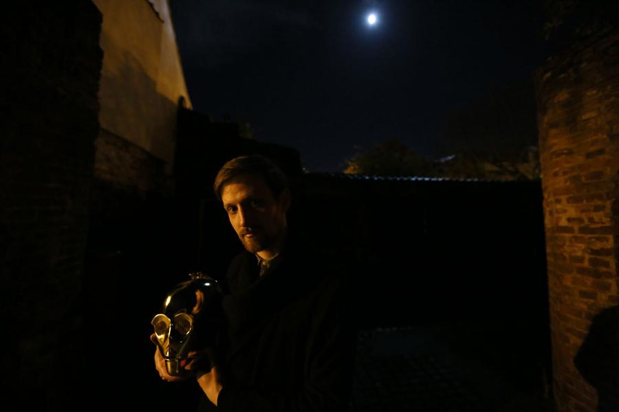 Энтузиаст Саймон Уилки позирует для фотографии с маской от наряда  С-3РО в Норвич, Англия, 24 ноября 2015.