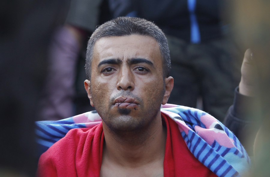 Мигрант с зашитым ртом в знак протеста, сидит на границе с Грецией возле села Гевгелия, Македония, 23 ноября 2015
