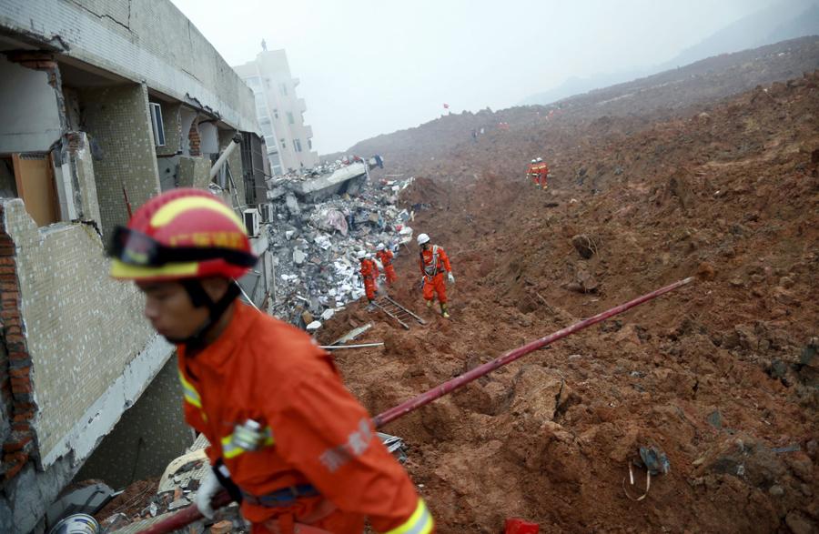 Пожарные ищут выживших возле поврежденного здания в месте оползня обрушившегося на промышленный парк в Шэньчжэне, Гуандун, Китай, 20 декабря, 2015 года.